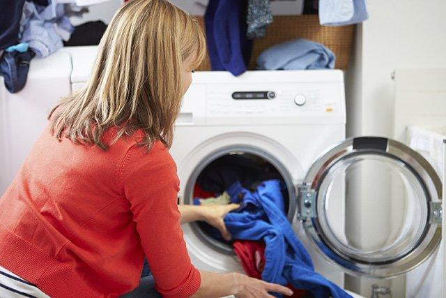 женщина достает одежду из стиральной машины