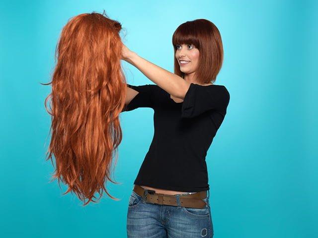 девушка держит в руках искусственный парик